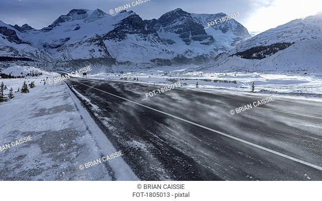 Snowdrift over remote road below snow covered mountains, Columbia Icefield, Alberta, Canada