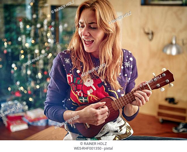 Blond woman playing ukulele in front of Christmas tree