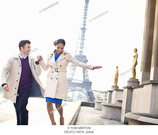 Couple walking in front of Eiffel Tower, Paris, France