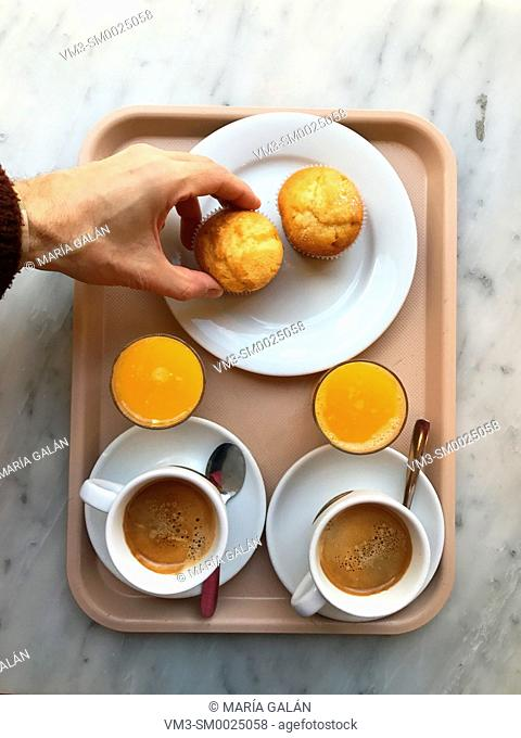 Two cups of coffee, two glasses of orange juice and two sponge cakes on a tray, and manâ. . s hand taking one of the sponge cakes. View from above