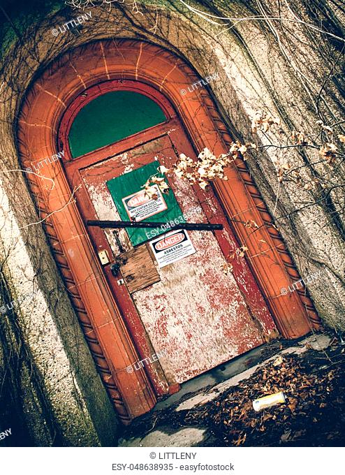 View of exterior of abandoned psychiatric hospital with asbestos warning on door