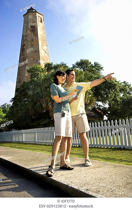 Mid-adult Caucasian couple sightseeing with lighthouse in background at Bald Head Island, North Carolina