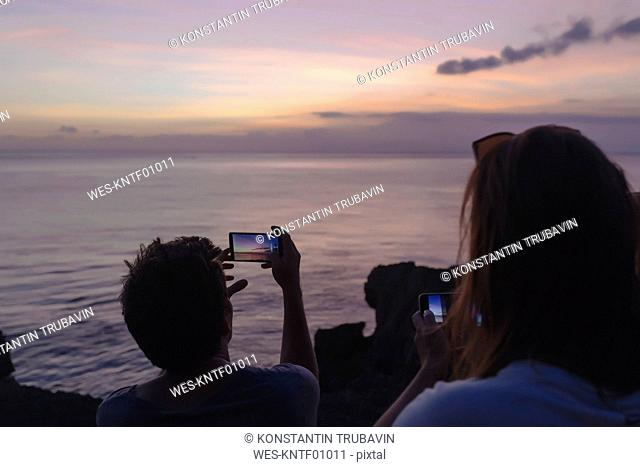 Indonesia, Bali, Lembongan island, friends at ocean coast at dusk taking cell phone pictures