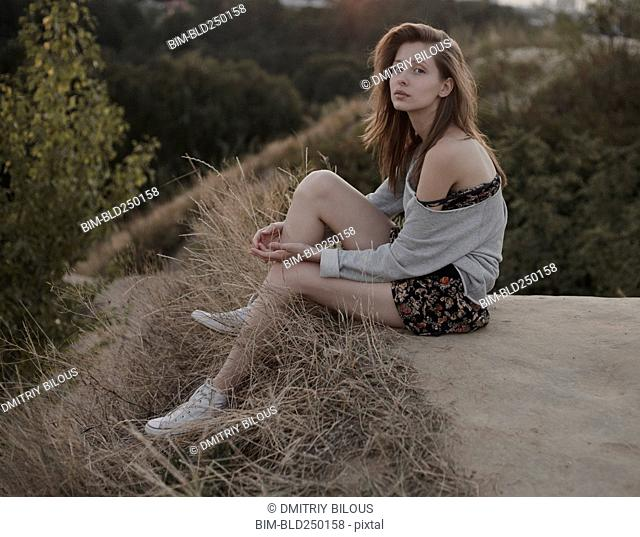 Serious Caucasian woman sitting on hill
