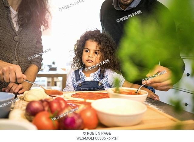 Family baking pizza in kitchen, daughter spreading tomato sauce