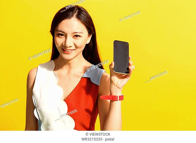 Young women show a mobile phone