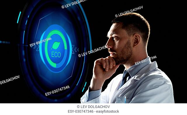 ecology, science and people concept - male doctor or scientist in white coat looking at virtual projection with eco icon over black background