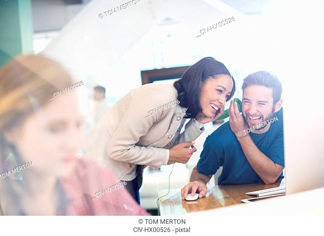 Creative business people sharing and listening to headphones in office