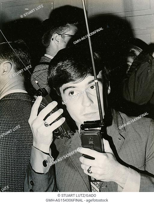 A student speaks on two walkie talkie portable radios at once while coordinating an anti Vietnam War student sit-in protest at North Carolina State University