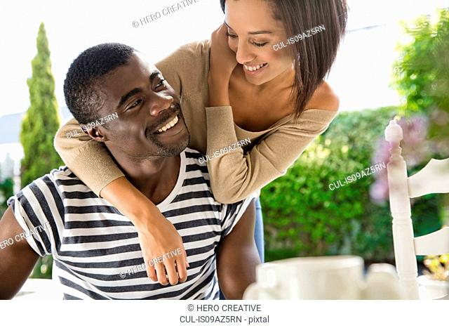 Young woman with arms around young man