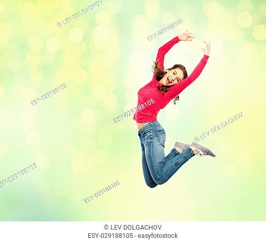 happiness, freedom, motion and people concept - happy young woman jumping or dancing in air over summer green lights background