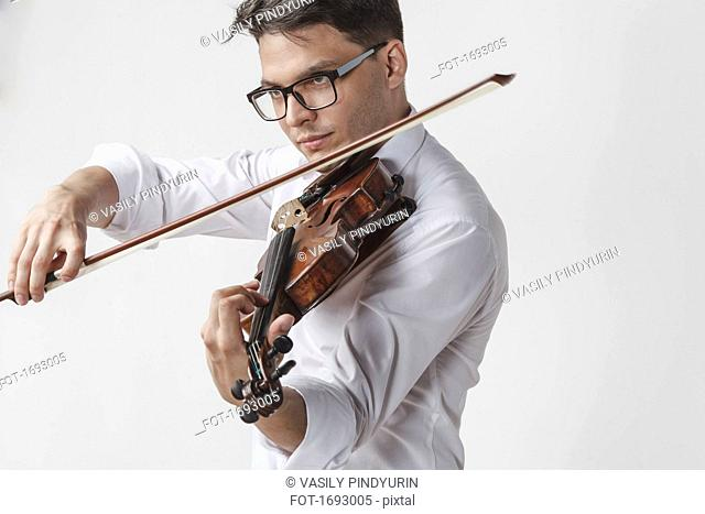 Confident young man playing violin against white background