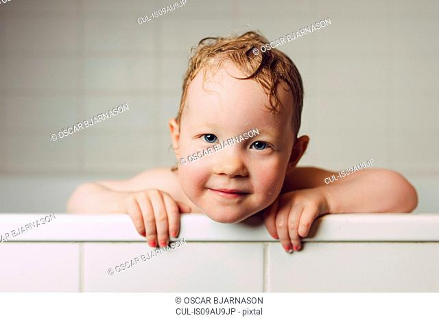 Portrait of girl with wet hair in bath holding onto edge looking at camera smiling