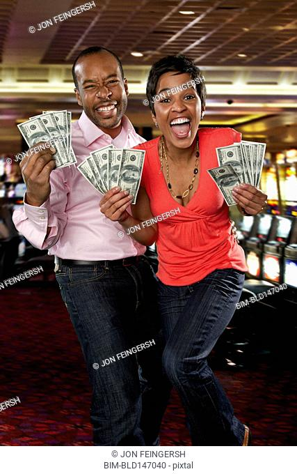 Excited couple holding cash winnings in casino