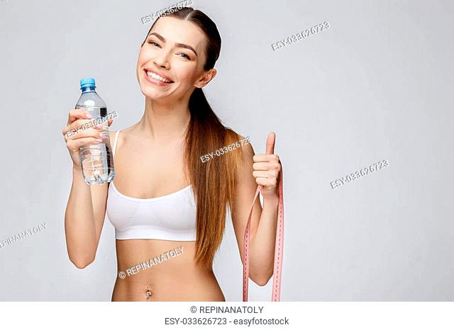 young sporty woman over gray background drinking water