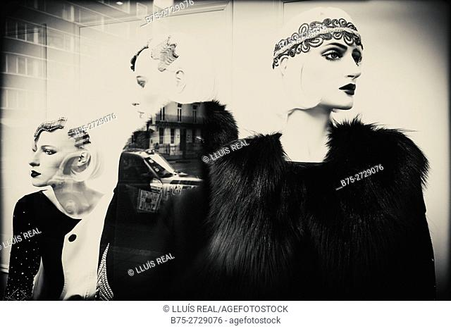 Fashion store, show window. Three female mannequins with elegant clothes, hairstyles and make up. Reflections on glass. London, England