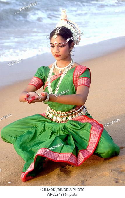 Dancer performing classical traditional odissi dance in front of bay of Bengal sea , Konarak , Orissa , India MR 736D