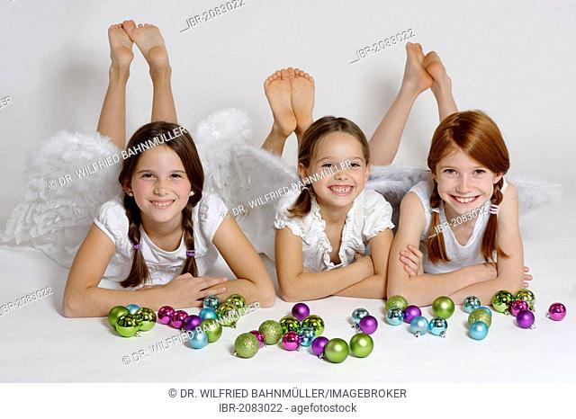 Three girls dressed up as Christmas angel, Christ Child with Christmas baubles
