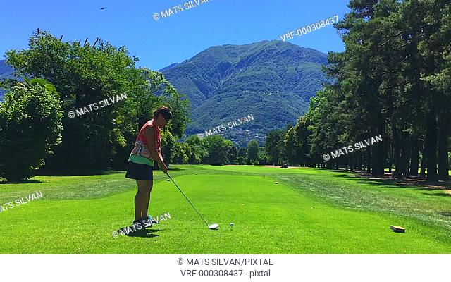 Woman Playing Golf on Fairway with Mountain in Background in Switzerland