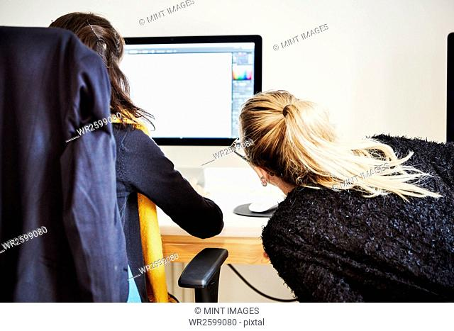 Two women seated sharing a computer screen and discussing the graphic content
