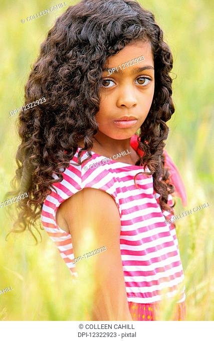 Portrait of a young girl with dark, curly hair and big brown eyes; Vancouver, Washington, United States of America