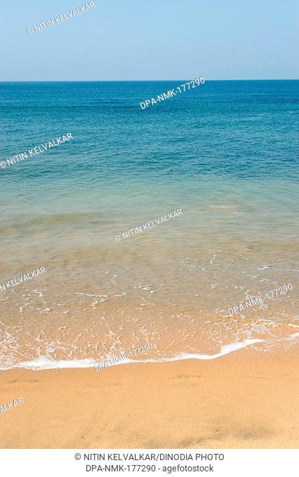 Sand and blue water of arabian sea at anjuna beach , Goa , India