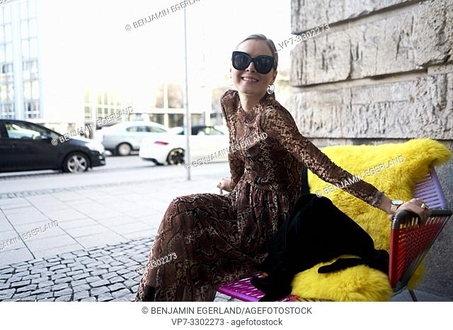 fashionable woman sitting in chair at street, in Munich, Germany