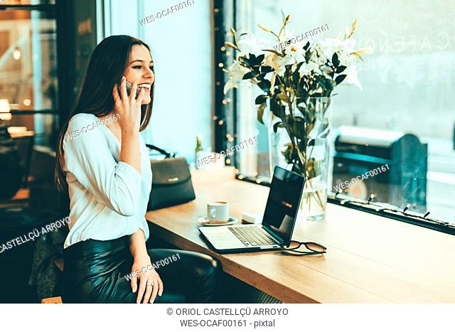 Happy young businesswoman on the phone in a coffee shop