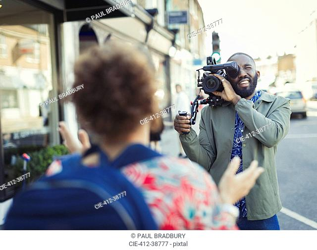 Young man with video camera videoing woman on street