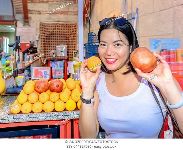 Beautiful woman shows fruits in front of fruit juice stall in Istanbul,Turkey