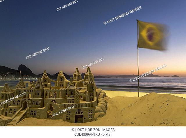 Sandcastle and Brazilian flag on Copacabana beach, Rio De Janeiro, Brazil