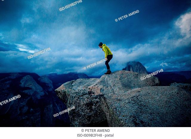 Mid adult man standing at top of mountain peering over edge, Yosemite National Park, California, USA