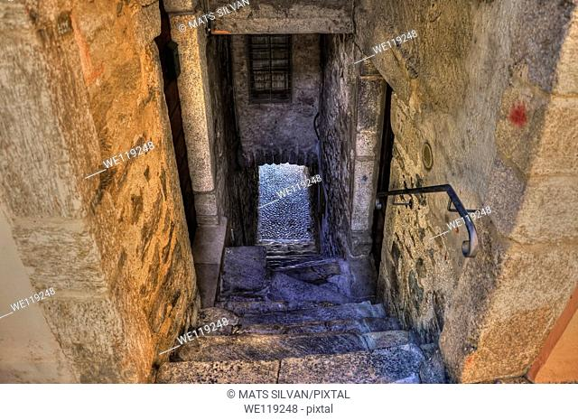 Old colorful stone alley with stairs down