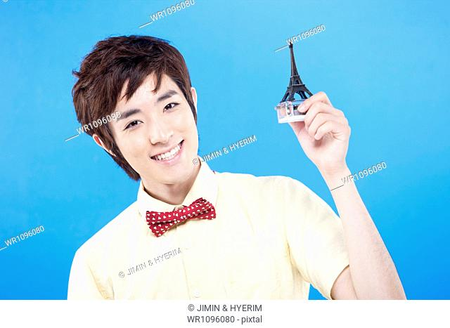 a man in white shirt with red tie playing with Eiffel tower toy