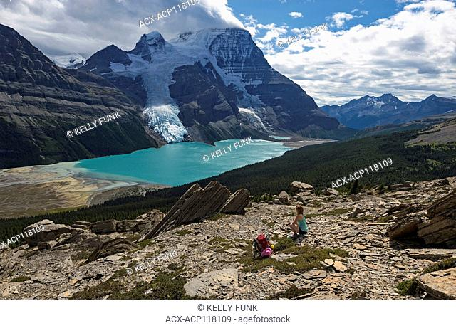 A young woman rests while on the Mumm Basis trail with Mt. Robson and Rearguard mountain in the background, Mt. Robson Provincial Park, British Columbia