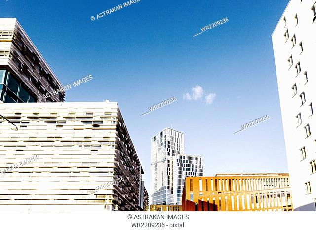 Low angle view of modern city buildings against blue sky