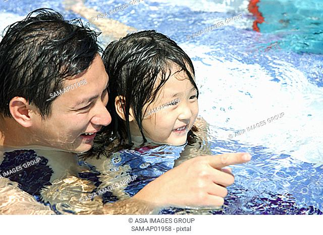 Father and daughter in swimming pool, father pointing with finger