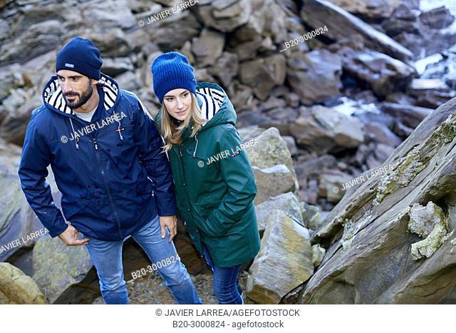 Couple at the coast of Santa Clara Island, Donostia, San Sebastian, Gipuzkoa, Basque Country, Spain, Europe, Raincoat, Winter