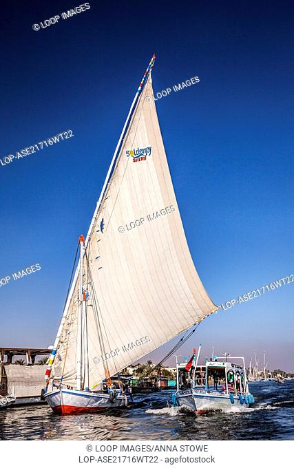 A ferry boat and felucca take tourists across the Nile at Luxor