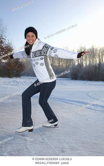 Germany, Bavaria, Woman ice skating, smiling