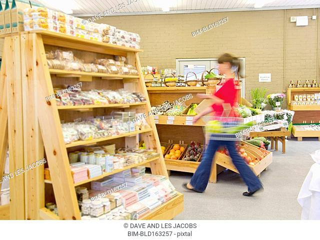 Blurred view of Caucasian woman shopping in grocery store