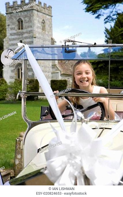 Flower girl (10-12) pretending to drive vintage car, tower in background, smiling, portrait