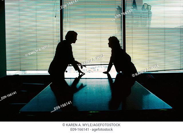 Man and woman in business attire, silhouetted, leaning on polished table from opposite sides, confronting each other, in conference room, with window behind