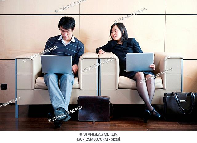 Man, woman working while waiting