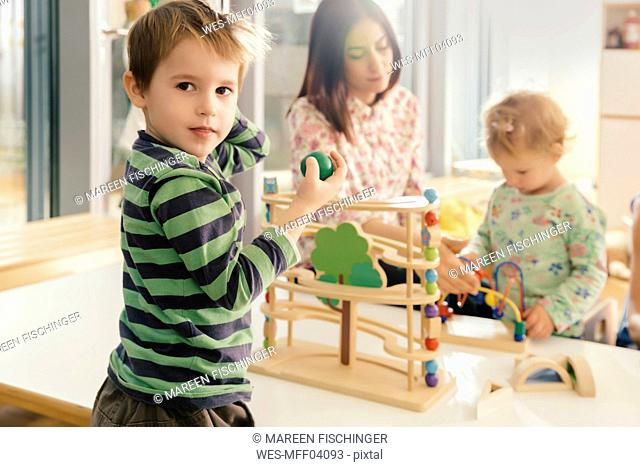 Boy looking up from playing with toys in kindergarten