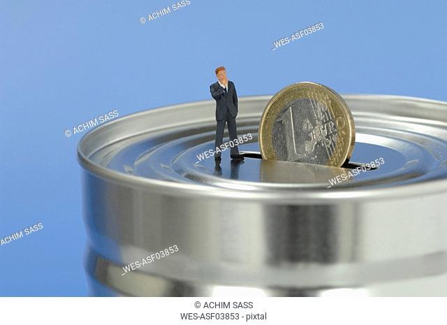 Businessman figurine standing on money box