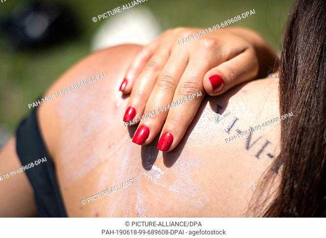 17 June 2019, Bavaria, Munich: ILLUSTRATION - A woman creams herself with sunscreen. Summer, sun, holidays - many people are looking forward to recovering from...