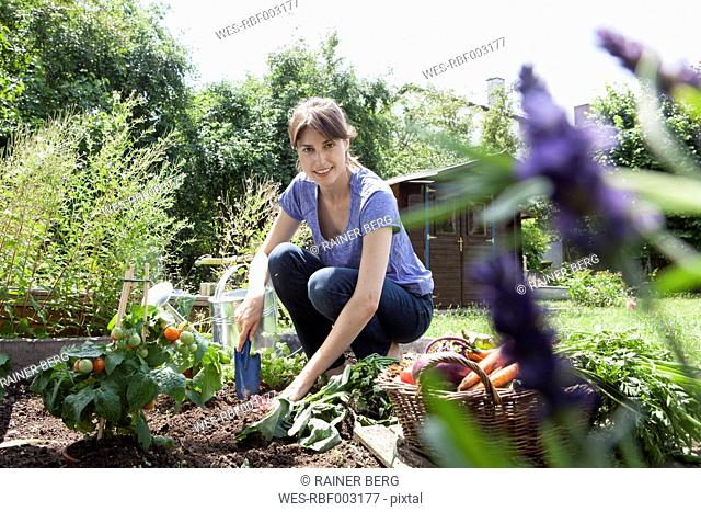 Smiling woman gardening in vegetable patch