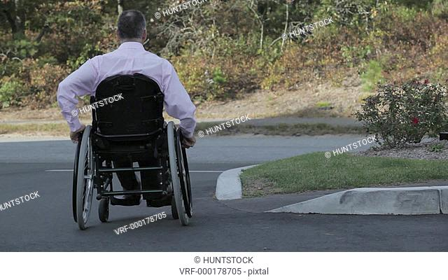 Man with spinal cord injury in a wheelchair using accessible street to sidewalk ramp