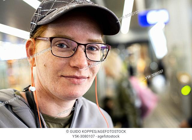 Tilburg, Netherlands. Portrsit of a redheaded female commuter wearing a cap and glasses, upon arrival at Tilburg's central railway station